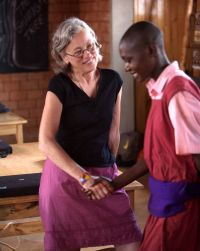 Susan Gold speaks with a young man while working in Africa