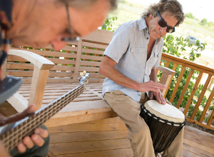 Jim Flickinger plays a bongo drum in the UW Health Rehabilitation Hospital gazebo while his brother, Mike, plays guitar