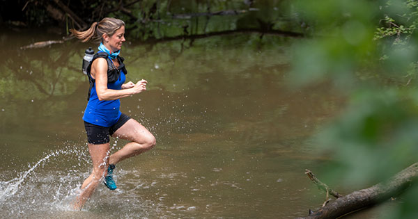 Tracey Hulick running through a creek