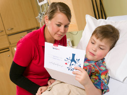 American Family Children's Hospital volunteer reading to young patient.