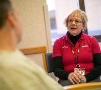 UW Health volunteer talking to a patient.